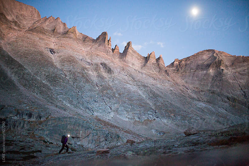 Young Adult Female Hiker walks in the moonlight through Rocky Mountain National Park by LORE for Stocksy United
