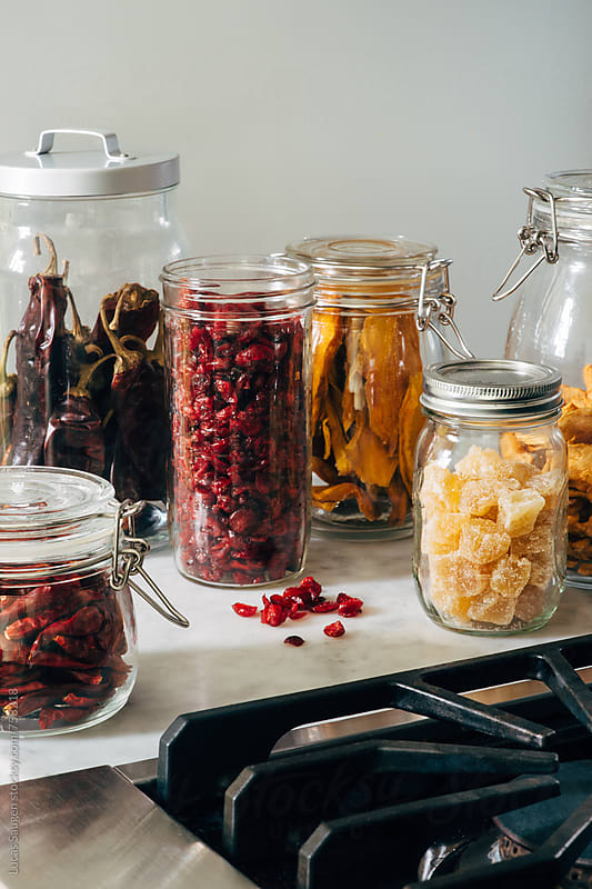 A collection of jar with dried fruits sitting on a counter top next to a stove in a kitchen. by Lucas Saugen for Stocksy United