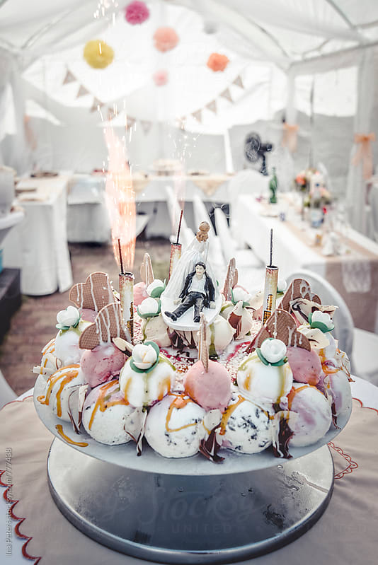 Food: colorful ice cream wedding cake with sparklers by Ina Peters for Stocksy United