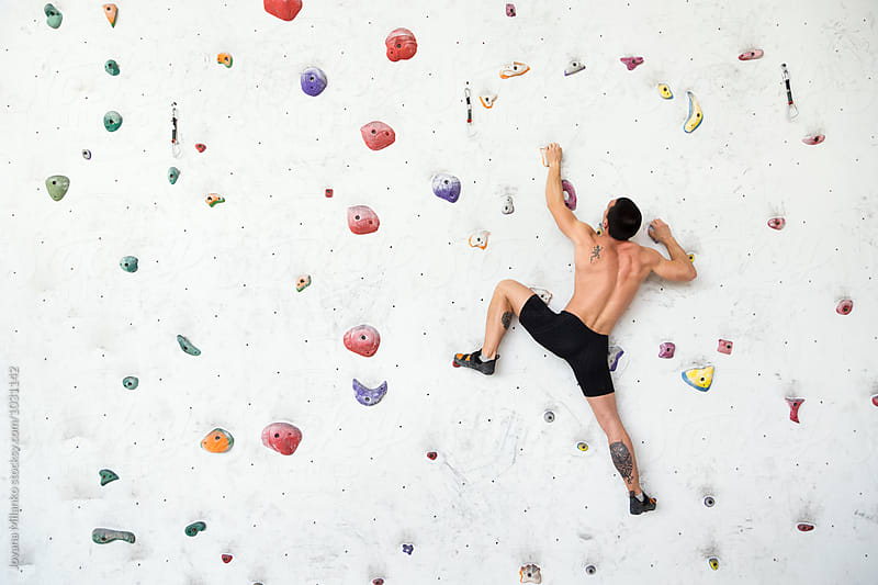 Free climber exercise on a colorful indoor boulder  by Jovana Milanko for Stocksy United