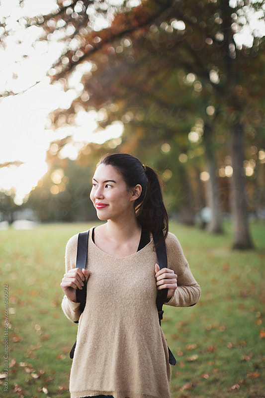 Young mixed race woman - asian & caucasian - outside with backpack on fall day by Rob and Julia Campbell for Stocksy United