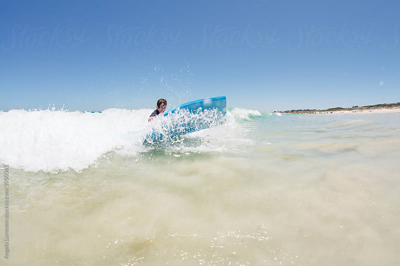 Boy having fun catching waves with a large foam mat at the beach in summer by Angela Lumsden for Stocksy United
