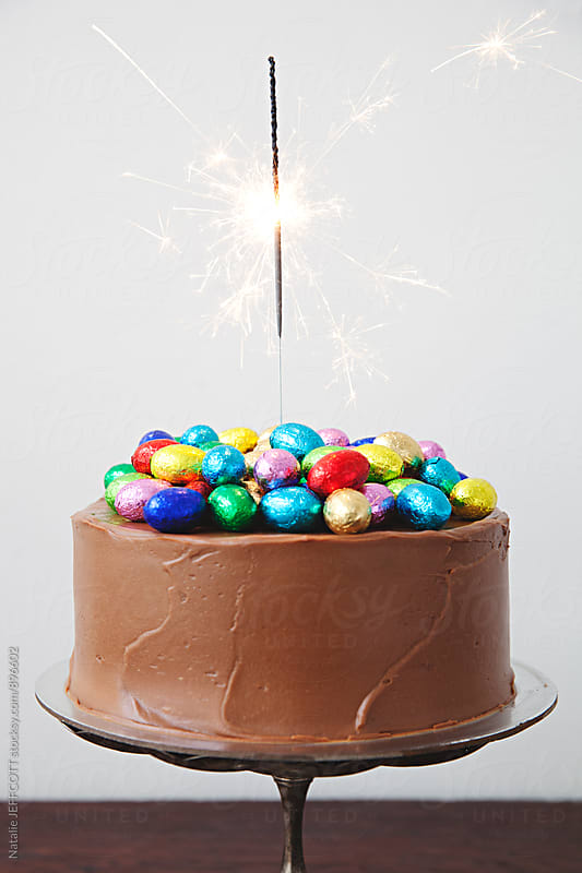 Decorated chocolate cake - with chocolate easter eggs and sparkler by Natalie JEFFCOTT for Stocksy United