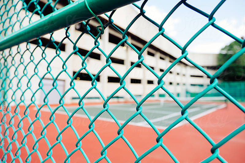 A tennis court in the background with a green fence in the foreground. by J Danielle Wehunt for Stocksy United