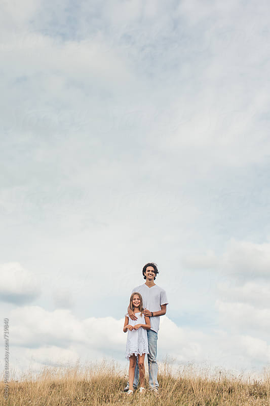Teenage boy and little girl standing in a golden field against a big sky by Cindy Prins for Stocksy United