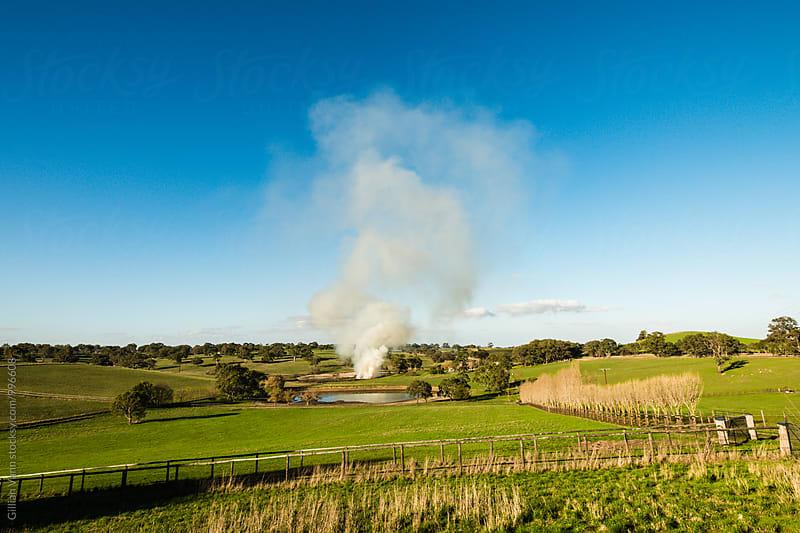 fire on a farm by Gillian Vann for Stocksy United