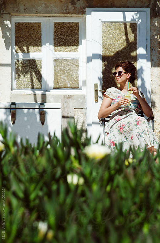 Brunette in floral dress drinking lemonade by Marija Anicic for Stocksy United