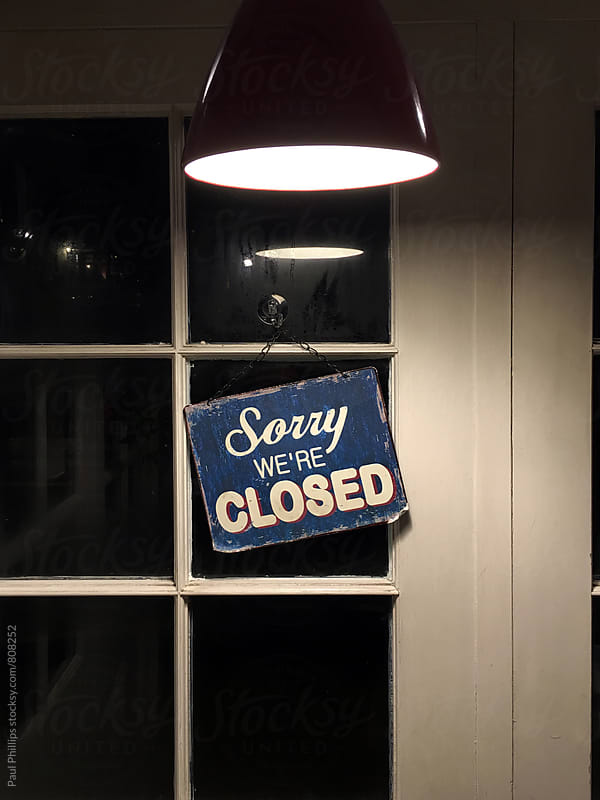Closed sign outside a restaurant with light shining down. by Paul Phillips for Stocksy United
