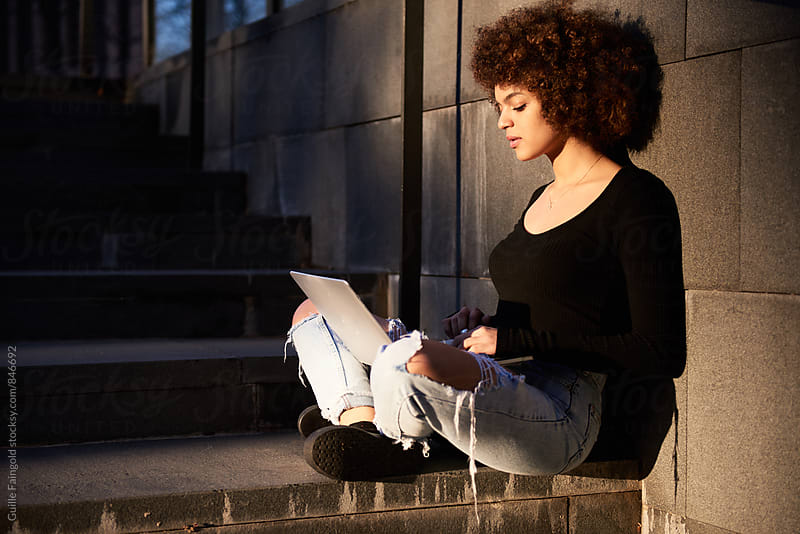 Side view of young woman using laptop while sitting in the street by Guille Faingold for Stocksy United