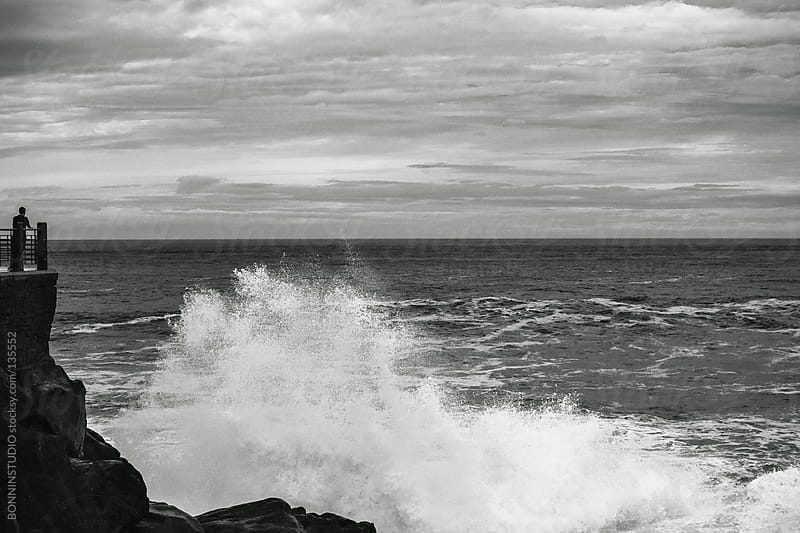 Man looking at the power of the sea. Black and white photo. by BONNINSTUDIO for Stocksy United