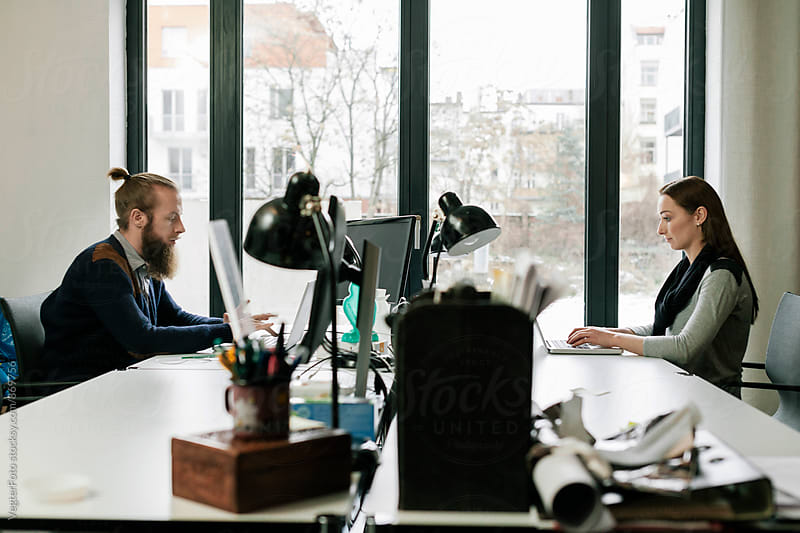 Two business people working at desk by VegterFoto for Stocksy United