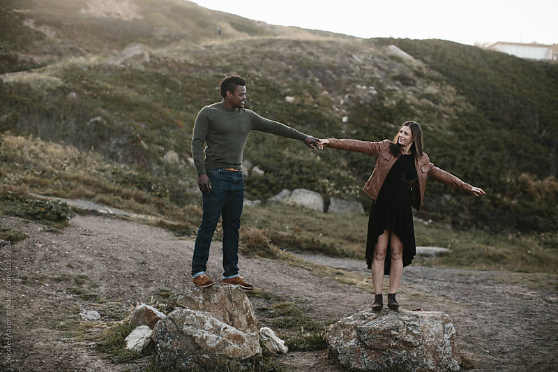 beautiful fashionable couple holding hands standing on rocks by Nicole Mason for Stocksy United