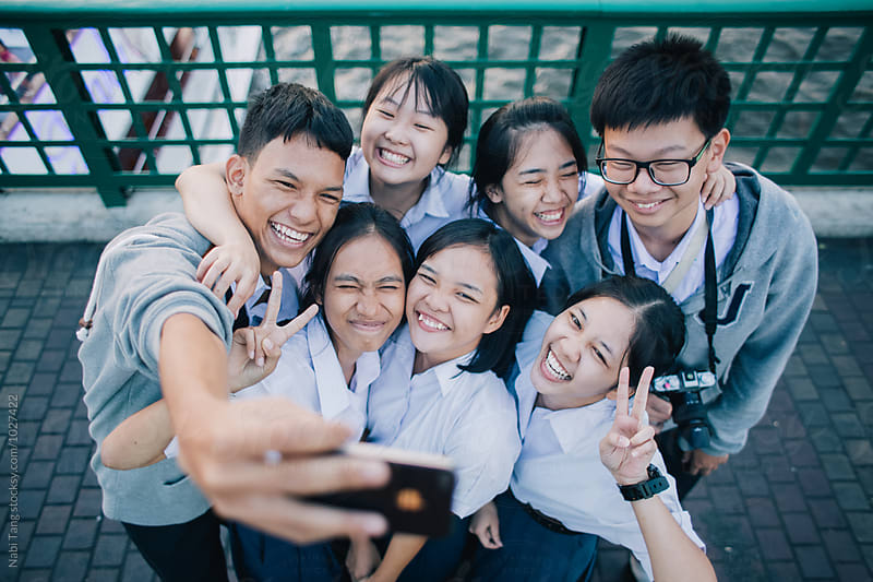 Group of young Asian students making self portrait with the phone by Nabi Tang for Stocksy United