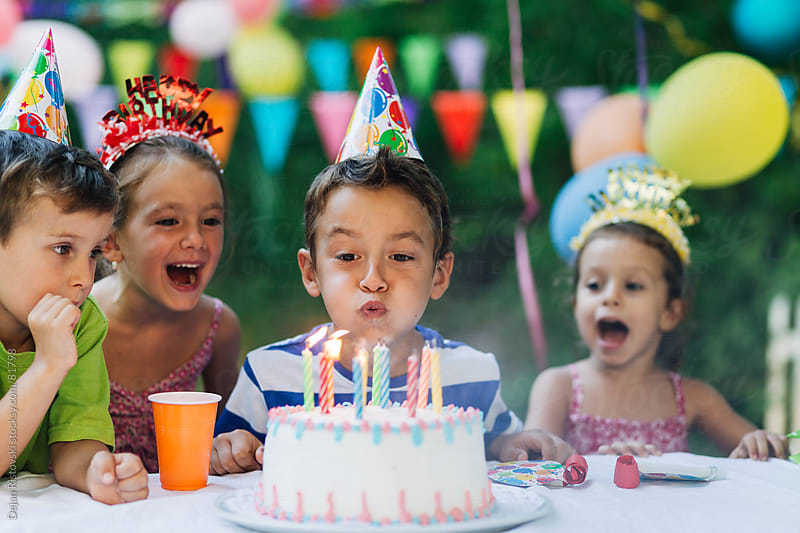 Child blowing birthday candles by Dejan Ristovski for Stocksy United