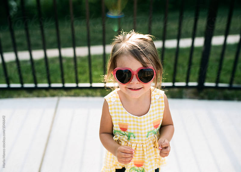 little girl in heart sunglasses by Maria Manco for Stocksy United
