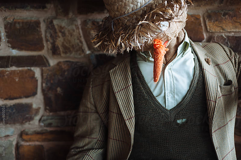 Scarecrow leaning against a brick wall by Suzi Marshall for Stocksy United