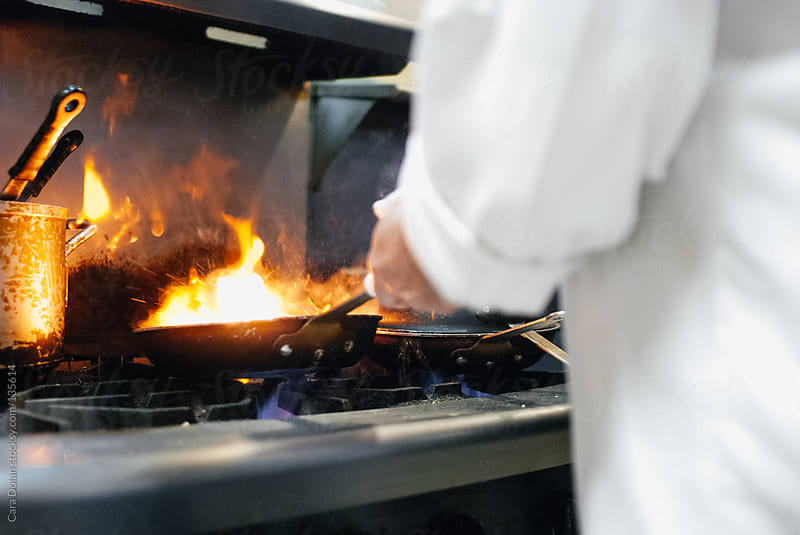 A chef cooks with a flaming fry pan in a restaurant kitchen by Cara Dolan for Stocksy United