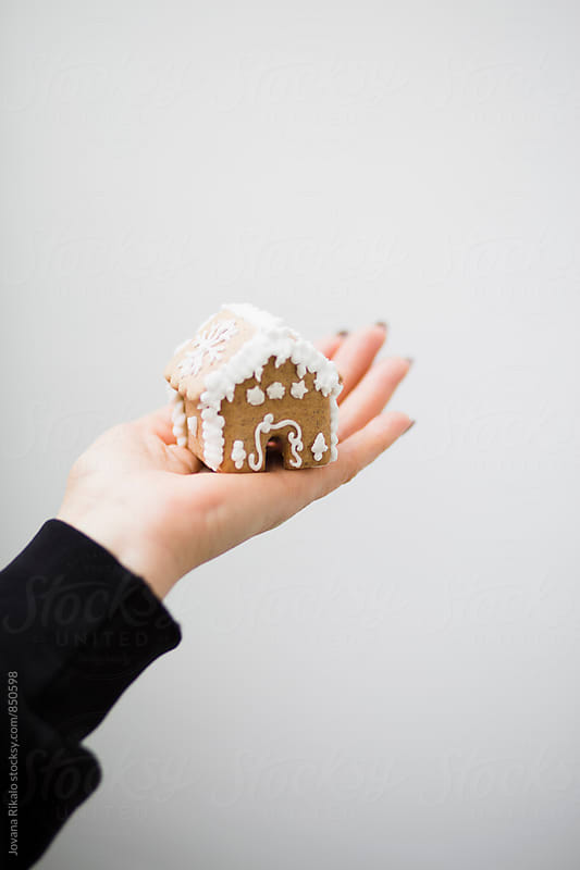 Woman holding small gingerbread house by Jovana Rikalo for Stocksy United