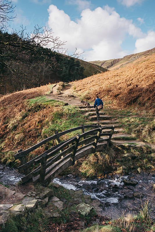Male and his dog crossing an old wooden bridge on a hillside. Edale, Derbyshire, UK. by Liam Grant for Stocksy United