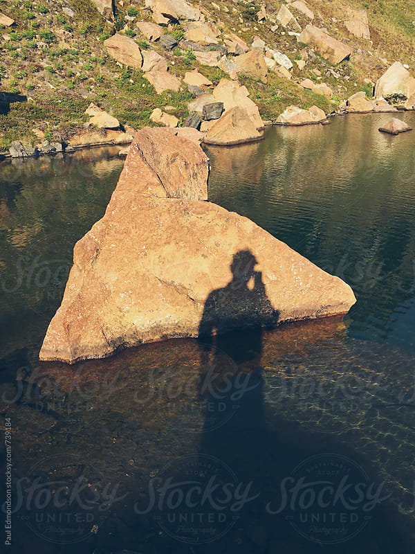 Photographer's shadow on rock and small lake, Central Cascades, WA by Paul Edmondson for Stocksy United