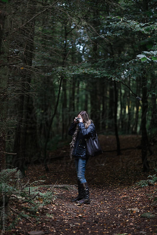 Woman taking photographs in the forest in autumn. by Darren Muir for Stocksy United
