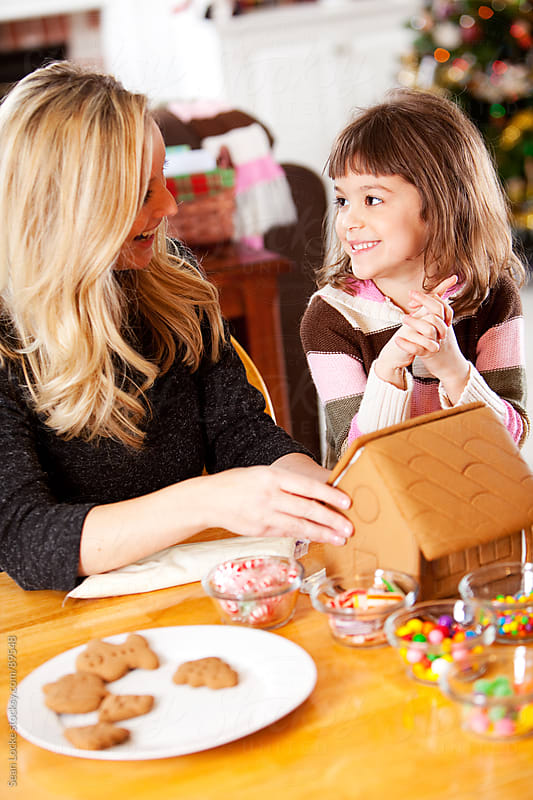Gingerbread: Teaching Daughter How to Decorate Gingerbread House by Sean Locke for Stocksy United