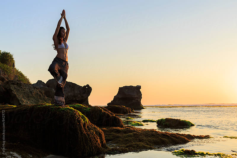 A young woman in a yoga pose at a beach by Felix Hug for Stocksy United