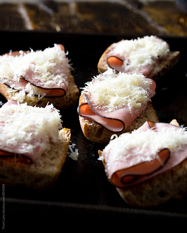 Several sandwiches with ham and cheese on baking tray by Trent Lanz for Stocksy United