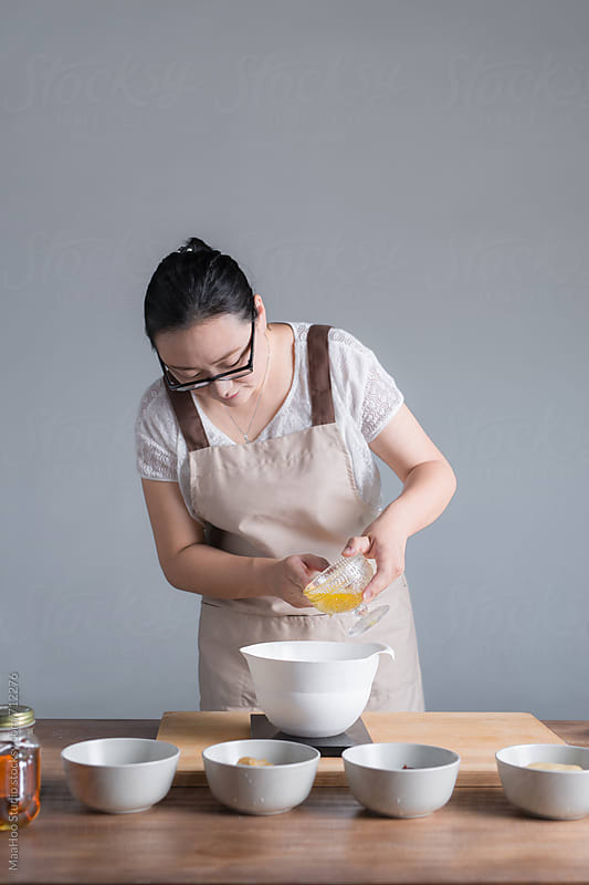 A young woman weighing oil while baking moon cake by MaaHoo Studio for Stocksy United