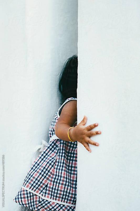 Small Burmese Girl Hiding Between White Temple Pillars by VISUALSPECTRUM for Stocksy United