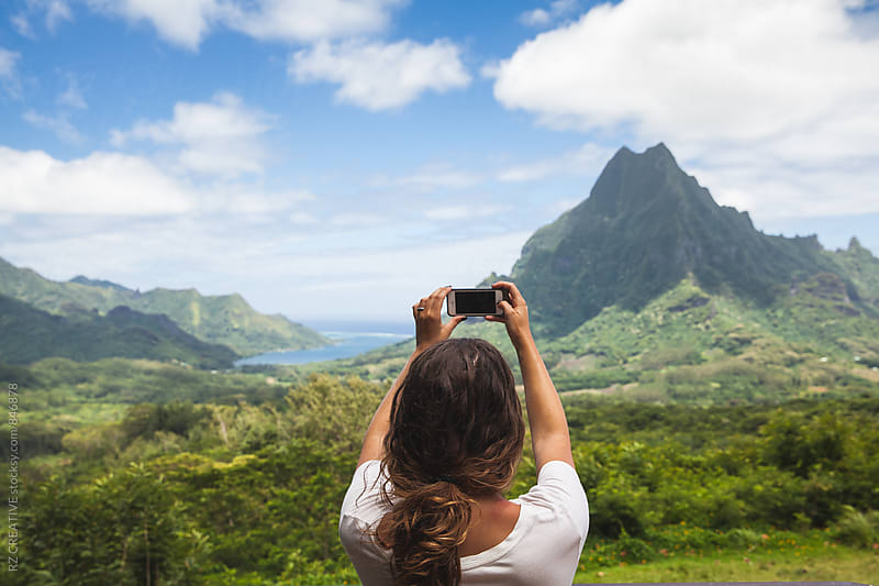 Woman taking a picture of beautiful island landscape with her cell phone. by Robert Zaleski for Stocksy United
