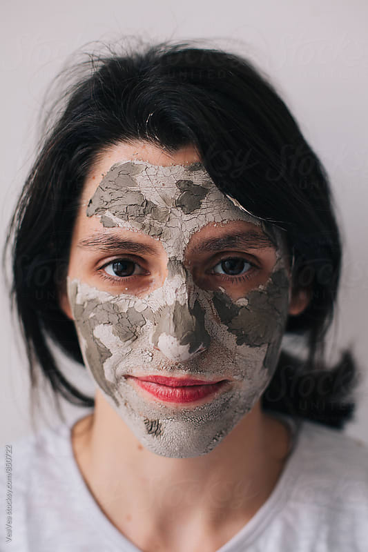 Beautiful brunette woman with home made facial mask looking at camera by VeaVea for Stocksy United