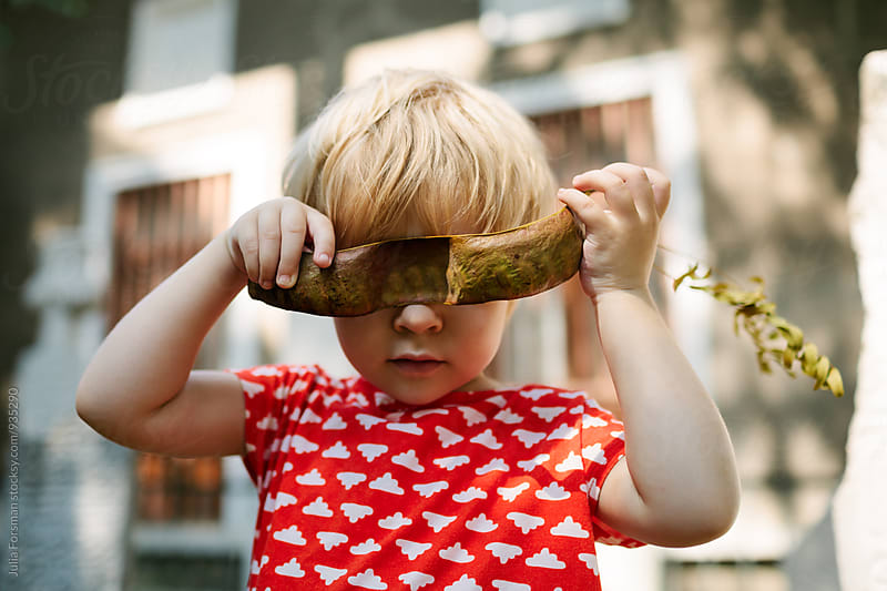 Little girl holds carob pod in front of her eyes. by Julia Forsman for Stocksy United