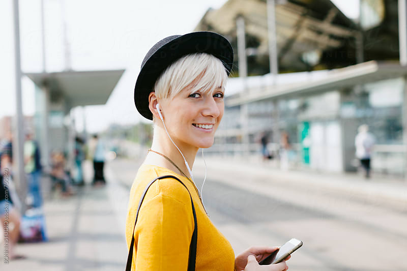 Portrait of a chic woman using her smartphone on the train station. by BONNINSTUDIO for Stocksy United