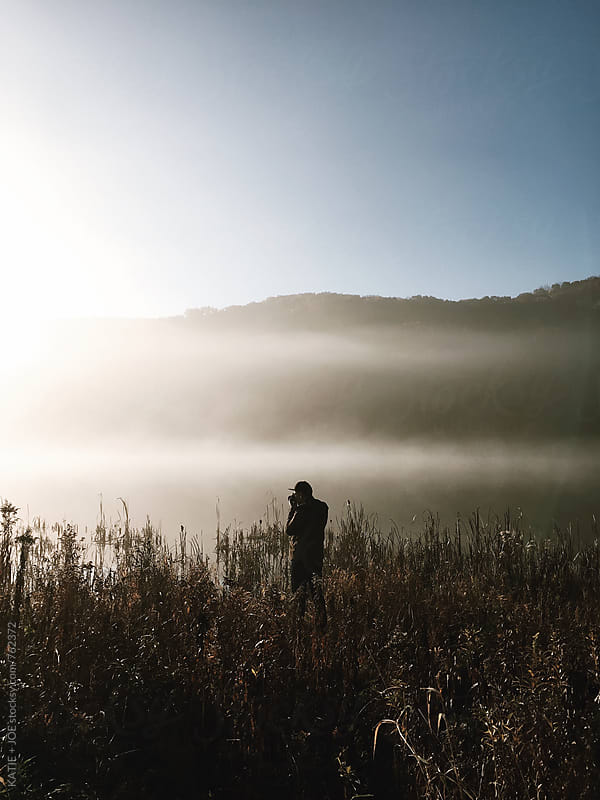 silhouette of a man in a field near a foggy lake by KATIE + JOE for Stocksy United