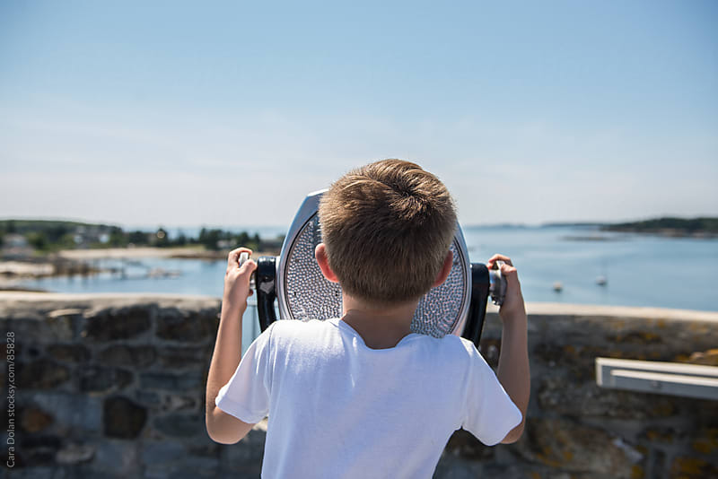 Boy looks through a tourist viewfinder at a scenic waterfront destination by Cara Dolan for Stocksy United