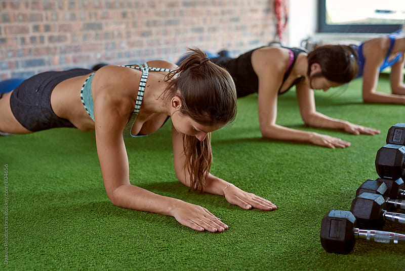 Muscular lean women doing push ups exercises planking at urban gym by Daxiao Productions for Stocksy United