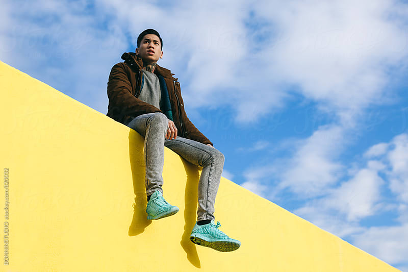 Portrait of an asian modern man sitting on a yellow wall. by BONNINSTUDIO for Stocksy United