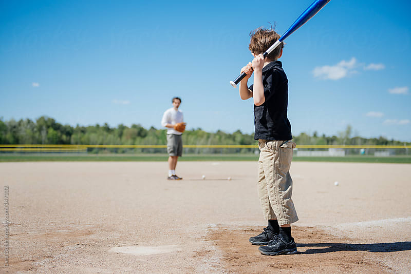 Boy and his father play baseball together by Cara Dolan for Stocksy United