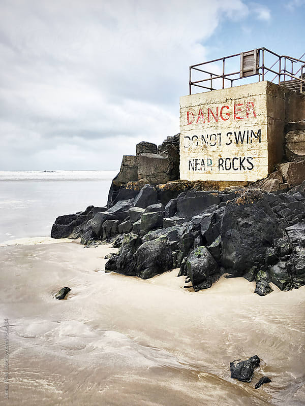 Warning sign by the sea by James Ross for Stocksy United