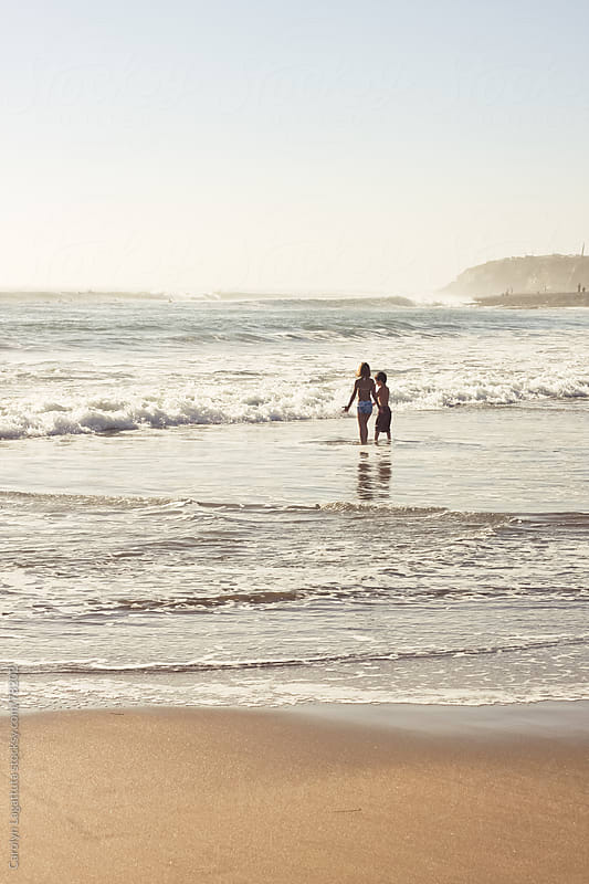 Girl and boy in the surf at the beach by Carolyn Lagattuta for Stocksy United