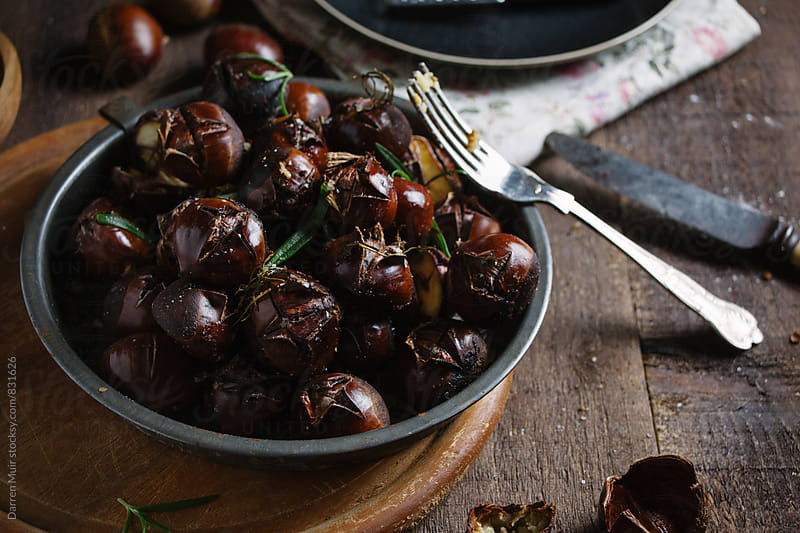 Freshly roasted chestnuts in a wooden background. by Darren Muir for Stocksy United