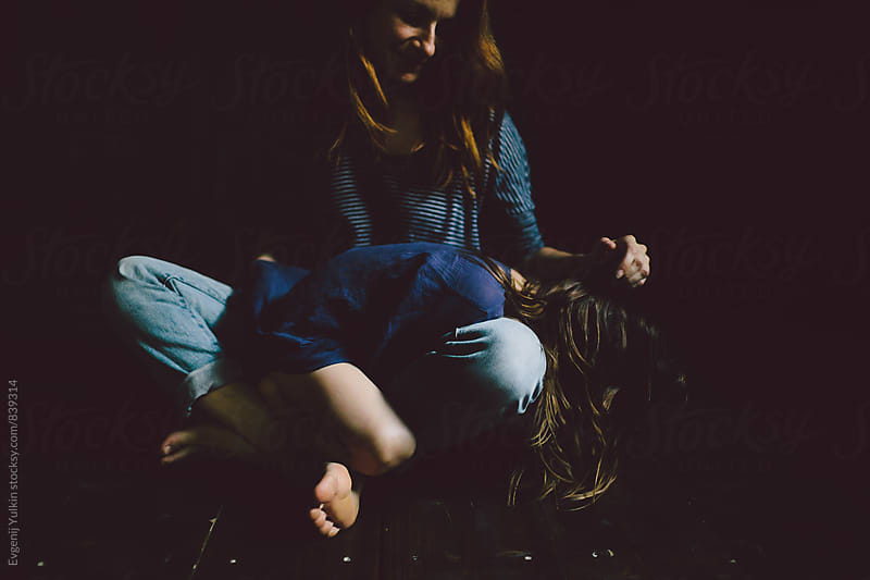 Mother caressing daughter's hair by Evgenij Yulkin for Stocksy United