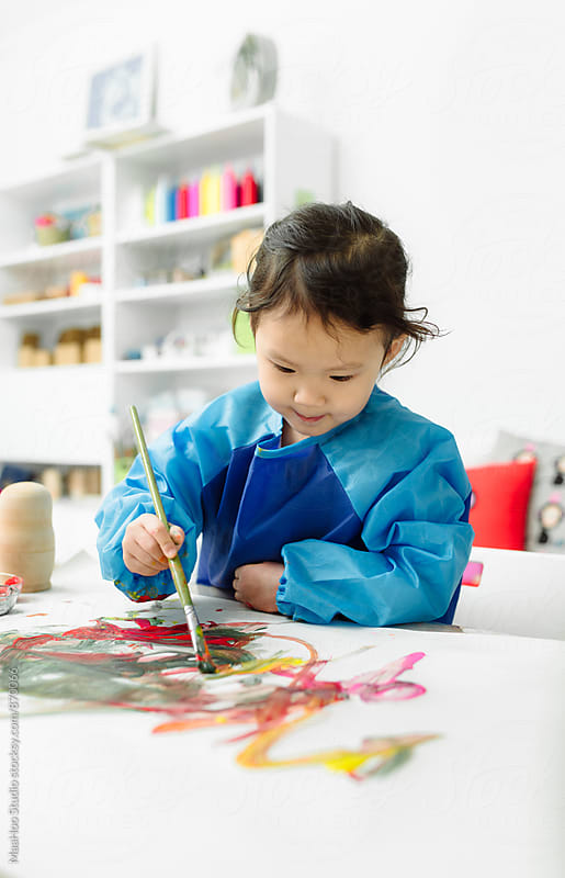 Little girl painting on paper by MaaHoo Studio for Stocksy United
