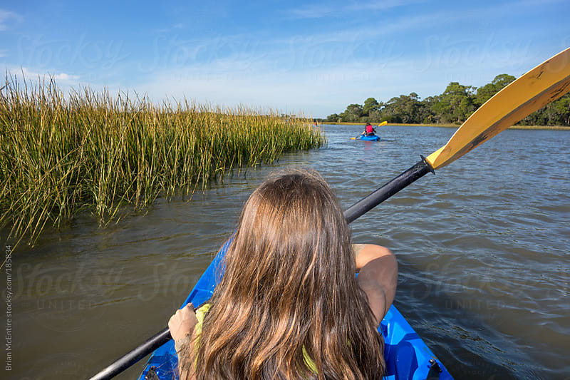 Little Girl Kayaking with Family in Distance on Salt Marsh Tour of Carolina Low Country by Brian McEntire for Stocksy United