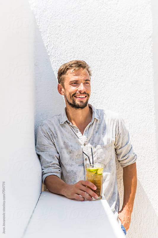 Bearded man drinking cocktail in a white bar by Jovo Jovanovic for Stocksy United