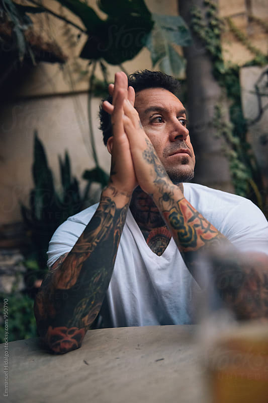 Tattooed male sitting and waiting at a table in a bar by Emmanuel Hidalgo for Stocksy United