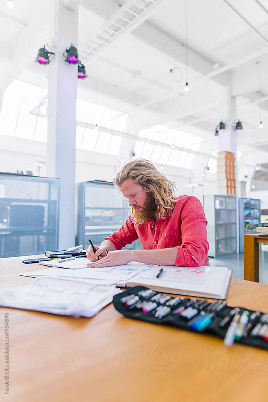 Young designer working behind a desk in spacious beautiful office or studio. by Ivo de Bruijn for Stocksy United