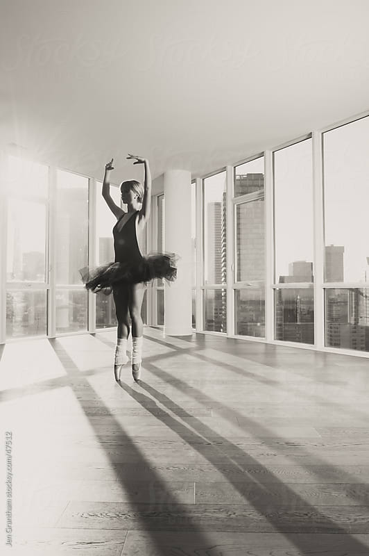 Ballerina dancing in front of a window by Jen Grantham for Stocksy United