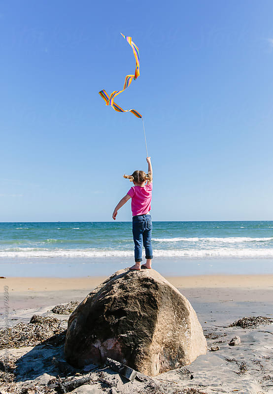 Girl on Beach with Wind Baton by Raymond Forbes LLC for Stocksy United
